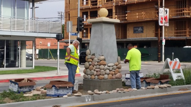 City workers applying rocks to the new Larchmont Monument on the northern end of Larchmont Boulevard at Melrose Avenue.
